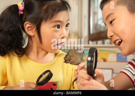 Young Children With Magnifying Glasses And Seeds - Stock Photo