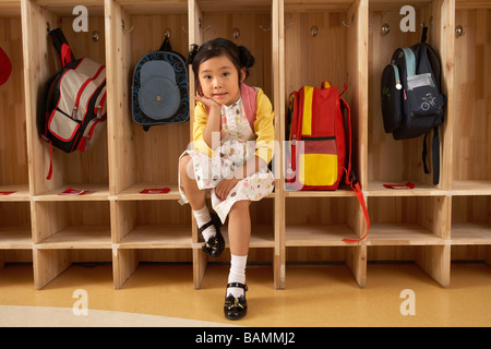Young Girl Sitting In Cloak Room - Stock Photo
