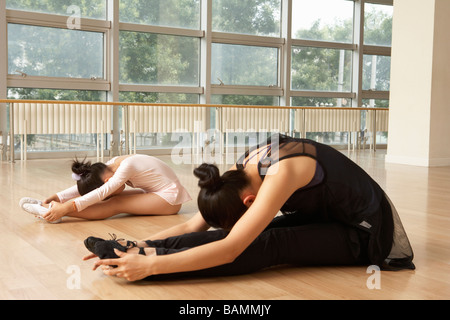 Ballet Dancers Stretching On Floor - Stock Photo