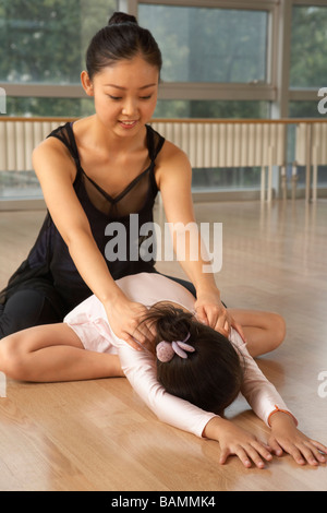 Ballet Teacher Helping Student Stretch - Stock Photo