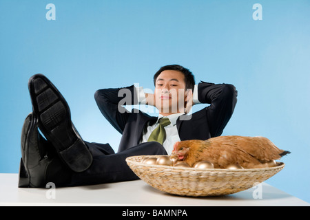 Businessman Relaxing Next To Chicken And Golden Eggs - Stock Photo