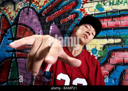 Teenage Boy Dancing In Front Of A Wall Of Graffiti - Stock Photo