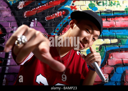 Teenage Boy Singing Into A Microphone In Front Of A Wall Of Graffiti - Stock Photo