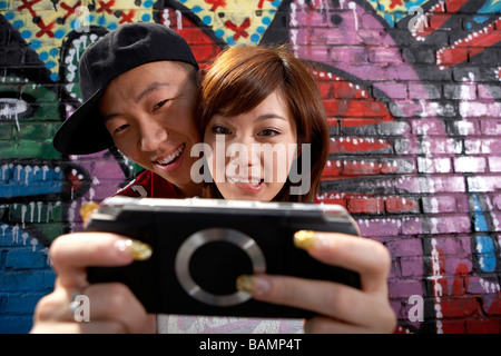 Teenage Boy And Girl Playing On A Game Console In Front Of A Wall Of Graffiti - Stock Photo