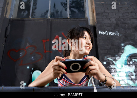 Teenage Girl Holding Personal Game Console - Stock Photo