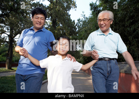 Little Girl Walking With Father And Grandfather Through The Park - Stock Photo