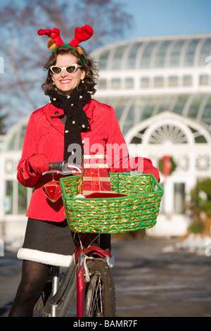 Woman in Christmas attire on a bicycle ride - Stock Photo