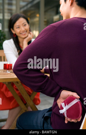 Young Man Surprising Girlfriend With Heart-Shaped Jewelry Box - Stock Photo