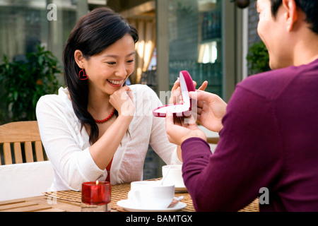 Young Man Presenting Jewelry Box To Girlfriend - Stock Photo