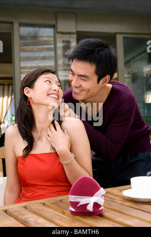Young Man Putting Necklace On Girlfriend - Stock Photo