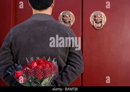 Young Man Waiting At Front Door With A Bunch Of Roses Behind His Back - Stock Photo