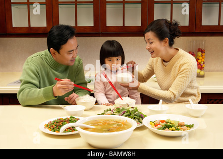 Parents trying to feed their daughter food - Stock Photo
