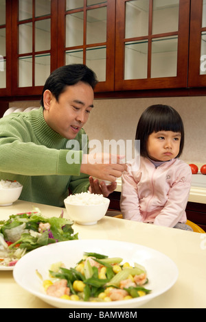 Man trying to feed his daughter - Stock Photo