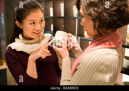 Two Young Women Looking At Objects In Shop - Stock Photo