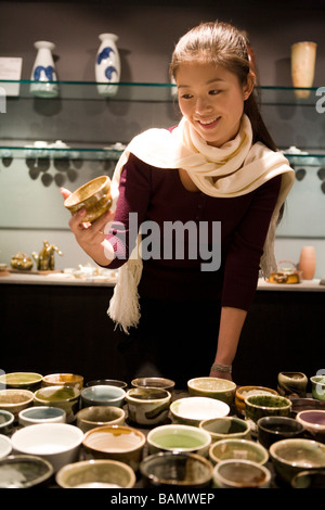 Young Woman Looking At Objects In Shop - Stock Photo