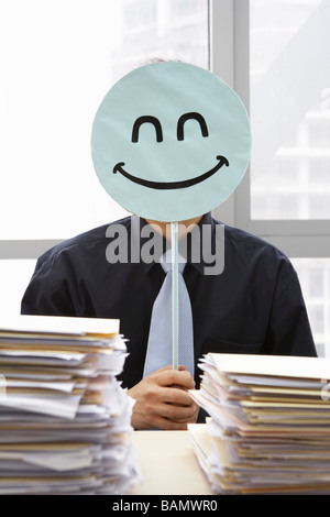 Businessman With Smiley-Face Sign - Stock Photo