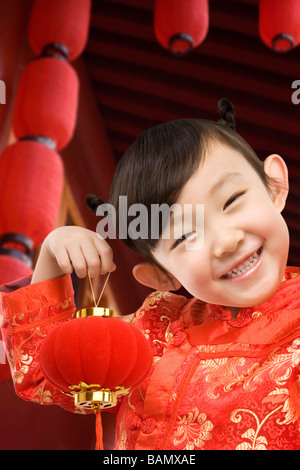 Young girl in festival Chinese New Year clothing, smiling at camera, holding Chinese lantern - Stock Photo