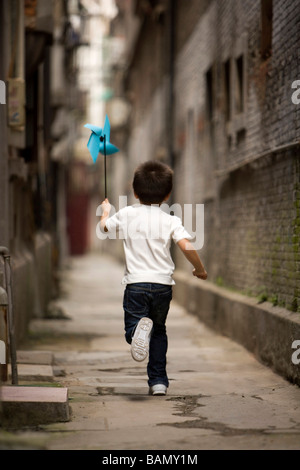 A child runs with a paper pinwheel - Stock Photo