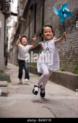 Children run with a paper pinwheel - Stock Photo
