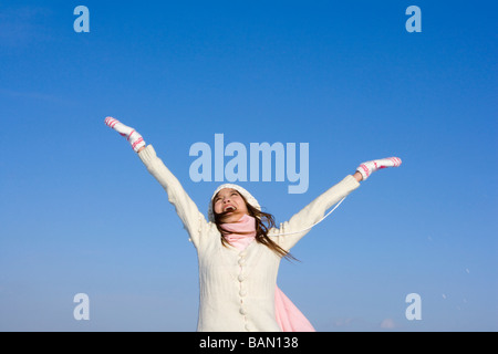 Young woman with her arms raised - Stock Photo