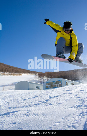 Young man on his snowboard mid-air - Stock Photo