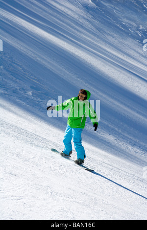 Young man snowboarding down a ski slope - Stock Photo