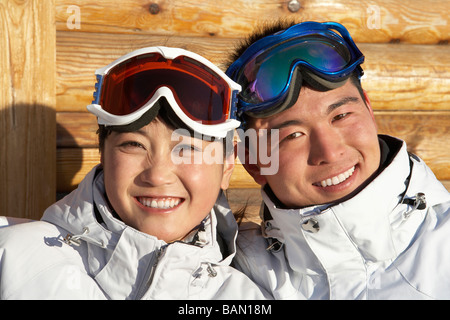 Young man and young woman in ski goggles smiling into the camera - Stock Photo