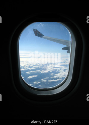 wing and sky at high altitude through the window of a passenger jet airliner - Stock Photo