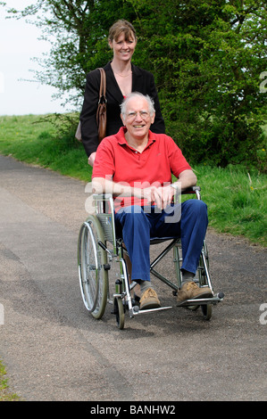 Female carer pushing elderly man in a wheelchair in the English countryside UK - Stock Photo