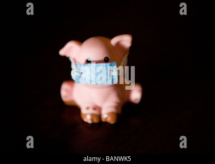swine flu concept shot, plastic pig wearing a mask - Stock Photo