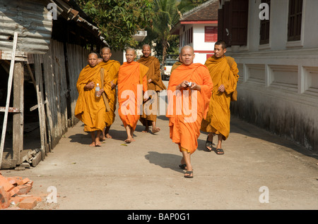 Monks take a stroll around the grounds of their temple in Luang Prabang Laos - Stock Photo