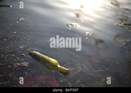 Green glass bottle floating in the East River, New York City, NY, USA 2009 - Stock Photo