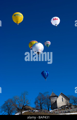 Hot air balloons above chapel on a blue sky: 2009 Chateau d'Oex International Hot Air Balloon Festival, Switzerland, - Stock Photo