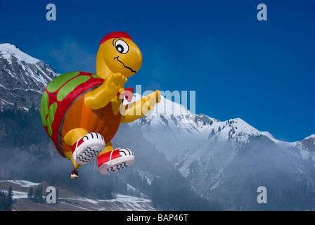 tortoise shape shaped balloon with blue skies and snow covered Alps: 2009 Chateau d'Oex international Hot Air Balloon Festival.