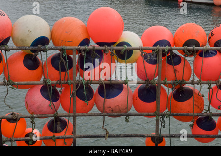 Orange buoys tied to the side of a commercial fishing trawler moored in the harbour at Weymouth in Dorset, England. - Stock Photo
