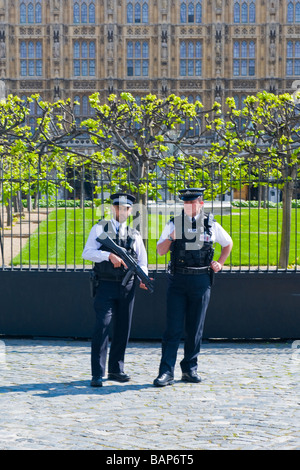 Parliament Square , Westminster , two armed metropolitan policemen in uniform stand on guard in sun outside House - Stock Photo