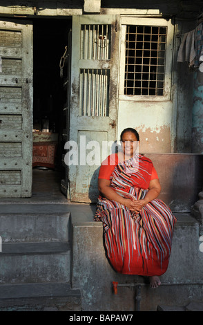 A Woman in a Red Sari relaxing in an Ahmedabad Street - Stock Photo