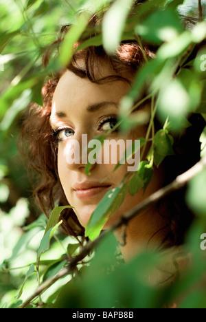 Woman's face behind green leaves, Winnipeg, Manitoba, Canada - Stock Photo