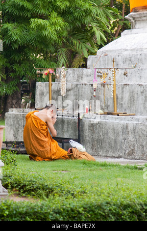 buddhist monk praying in front of a chedi at wat pra sing in chiang mai thailand - Stock Photo