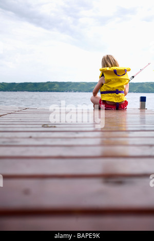 Young girl wearing life preserver fishing off the end of dock at Echo Lake, Saskatchewan, Canada - Stock Photo