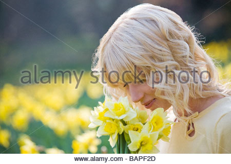A young woman smelling a bunch of daffodils - Stock Photo