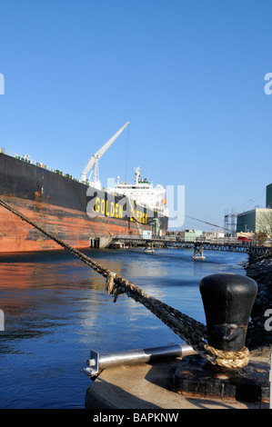 Oil tanker from Golden Energy tied up at terminal offloading fuel with power plant in background in Cape Cod Canal, - Stock Photo