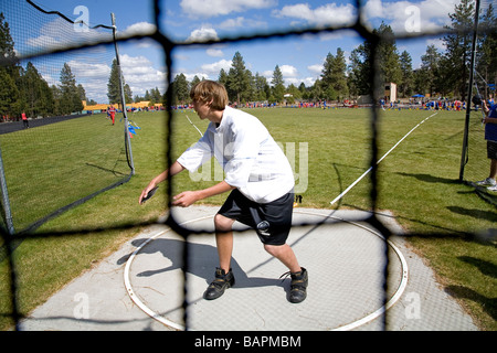 A middle school boys discus throw during a school track and field meet on the field of a local junior high school, - Stock Photo