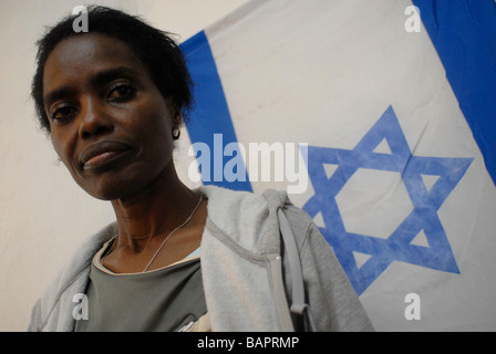 An African migrant with the Israeli national flag in Tel Aviv Israel - Stock Photo