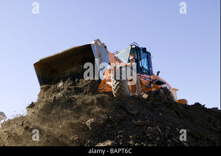 Front end loader excavating basements for new residential houses - Stock Photo