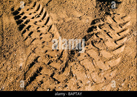 Tire track in the dirt from a front end loader excavating basements for new residential houses - Stock Photo