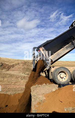 Dump truck dumping fill dirt into excavated basement for new residential houses - Stock Photo