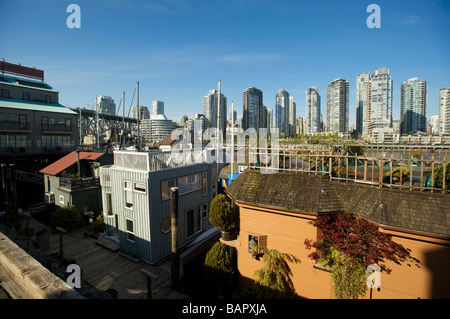 House boats in False Creek, with the Condo towers of Yaletown in the background.  Vancouver BC, Canada - Stock Photo