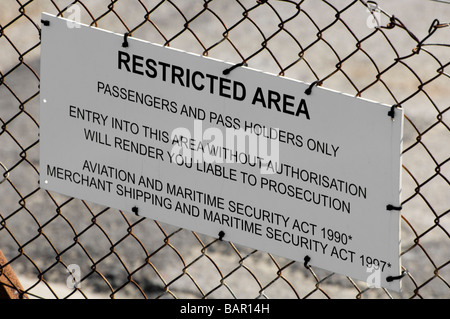 Restricted Area warning sign and fence protecting part of the port at Weymouth in Dorset, England, from unauthorised - Stock Photo