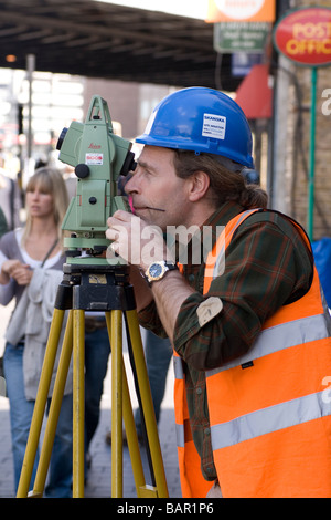 A surveyor uses a theodolite in a London street. - Stock Photo